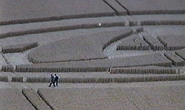 Video Frame 1 and 2: White object moving rapidly across triple crescent formation at Barbury Castle, August 7, 1999. People in formation do not seem aware of moving light. Video frames © 1999 by Donald Fletcher.