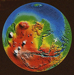 "This color coded map of Mars indicates highest altitudes in red and lowest in blue. The deep gash of Valles Marineris, lower center, stretches nearly 3000 miles and as much as 6 miles deep along the Martian equator, the largest canyon in the solar system. The white knobs west of the canyon are the large volcanoes in the Tharsis Montes region, including Olympus Mons, the largest volcano in the solar system. The white X marks the general region of Cydonia, site of the controversial 1976 Viking ""face."" Map courtesy NASA/JPL."