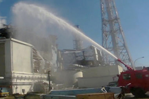 "Japanese fire truck spraying water on Fukushima Unit 3, the only reactor that contains MOX fuel, ""mixed-oxide"" that contains plutonium as well as uranium. Plutonium is the most dangerous radioactive material with a half-life of 24,000 years. If it is released in smoke and steam from a burning reactor, that plutonium can be inhaled and will contaminate soil downwind. Image by Japanese Defense Ministry."